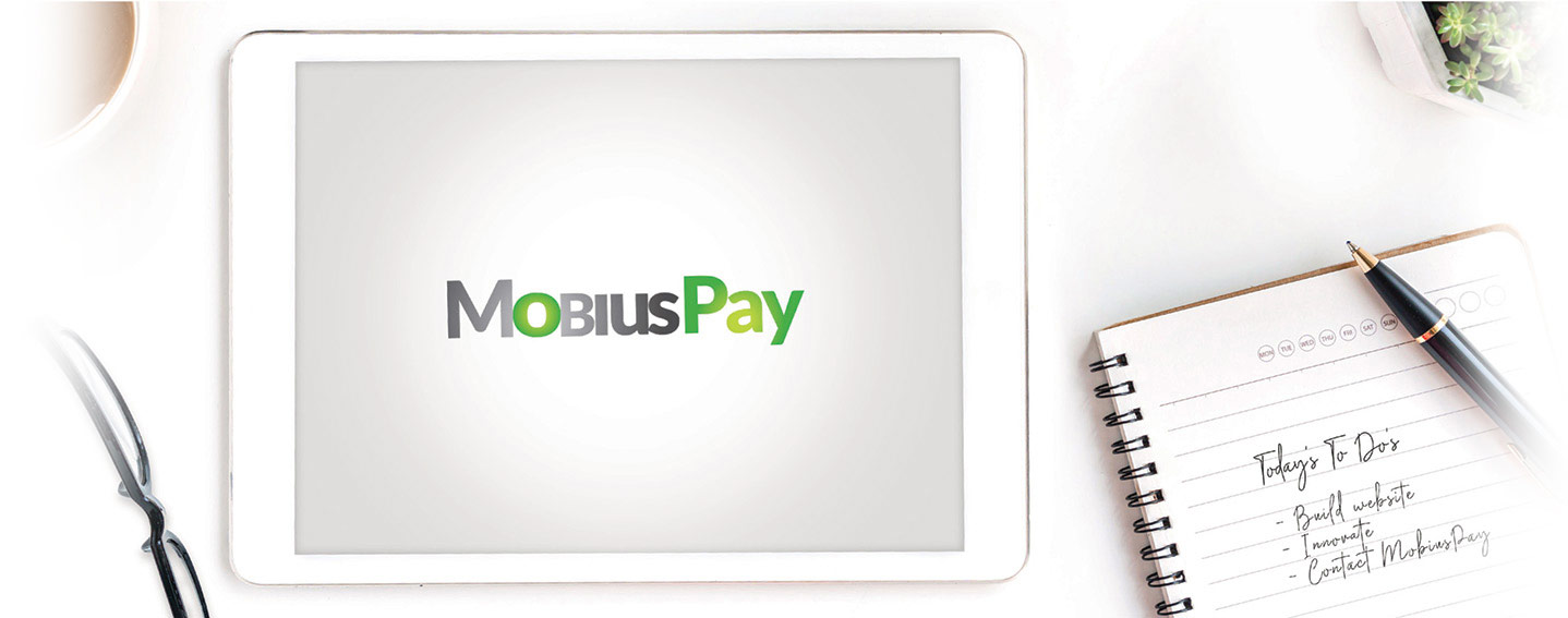 A table with a notepad, ipad, coffee and glasses to show the innovative things you come up with and how you should contact MobiusPay who does Credit Card payment processing supported by people with  years of banking knowledge.